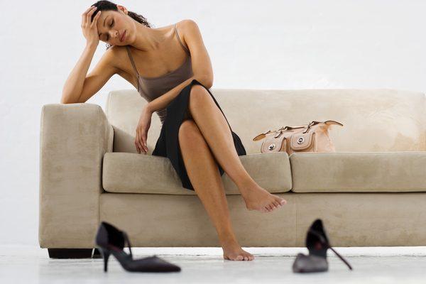 Девушка сняла туфли и сидит на диване