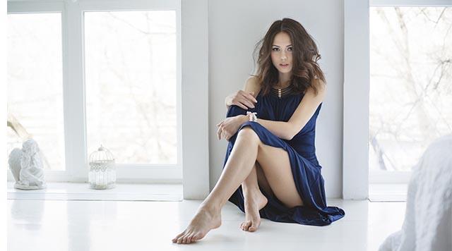 Девушка с красивыми ногами сидит в платье