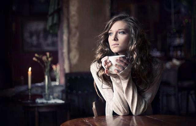Девушка сидит за чашкой кофе