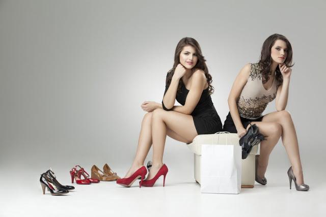 Девушки сидят на пуфе с обувью