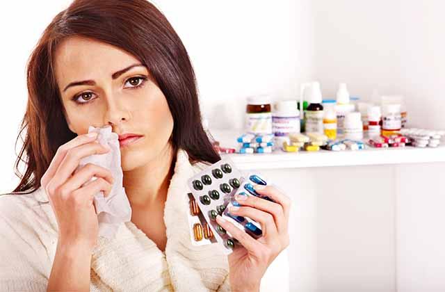 Девушка прикрывает рукой рот и держит таблетки