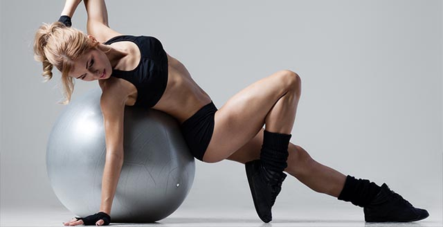 Девушка лежит спиной на гимнастическом шаре