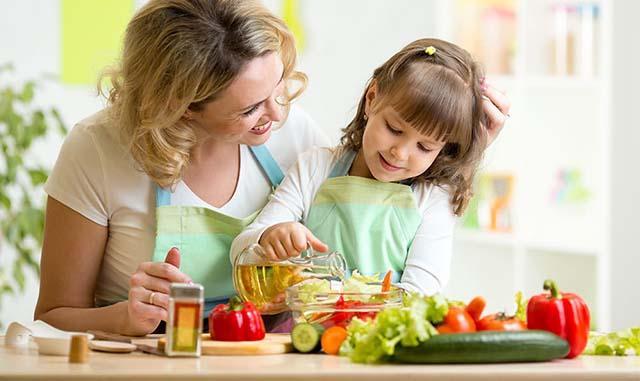 Мама с дочкой готовят салат