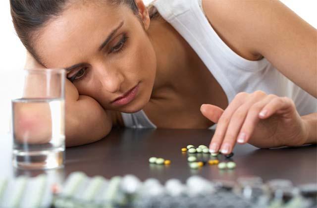 Девушка перебирает таблетки на столе
