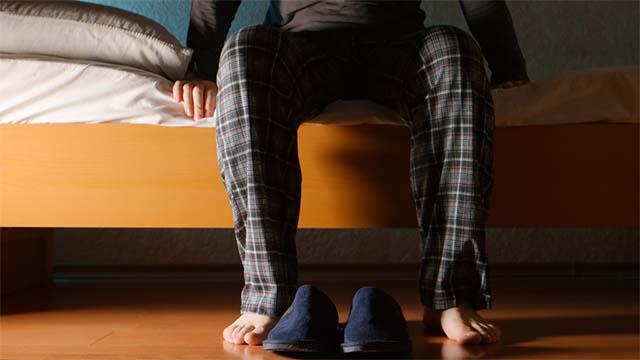 Мужчина в пижаме сидит на кровати