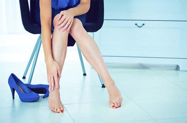 Девушка сняла каблуки и держит ноги