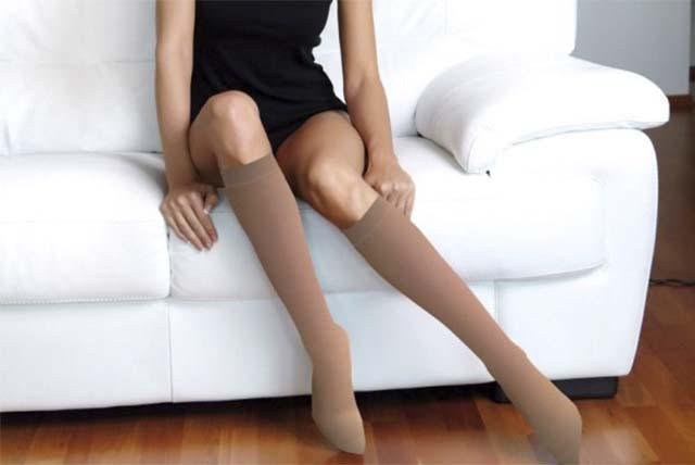 Девушка в чулках сидит на диване
