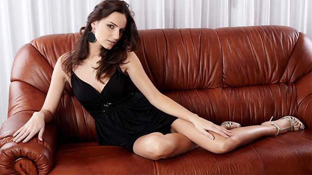 Девушка красиво сидит на диване