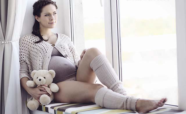 Беременная девушка сидит у окна