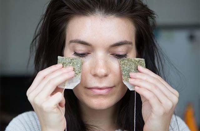 Девушка держит чайные пакетики под глазами