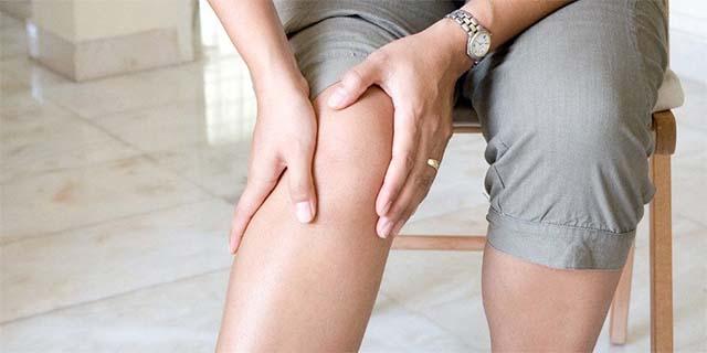 Женщина держится за правое колено