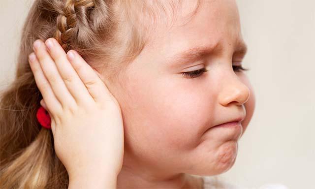 Девочка держит ухо