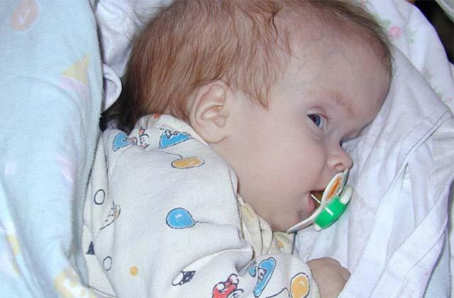 Новорожденный ребенок лежит с соской