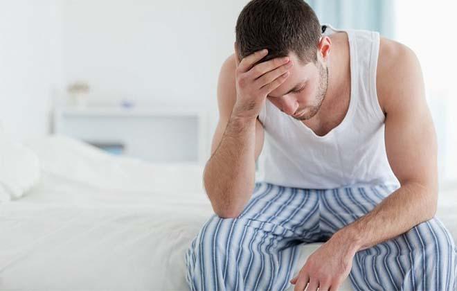 Мужчина грустный сидит на кровати